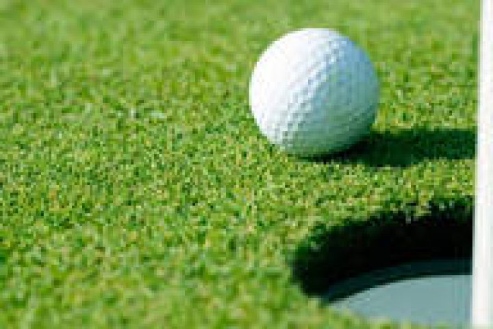 golf ball next to hole on the green