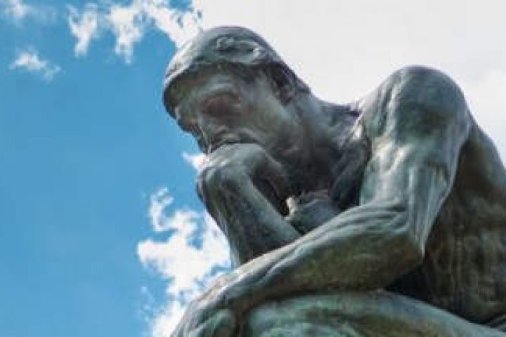 the Thinker set against a blue sky with white clouds