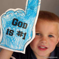 """boy holding paper hand with index finger sticking up; """"God is #1"""" written on hand"""
